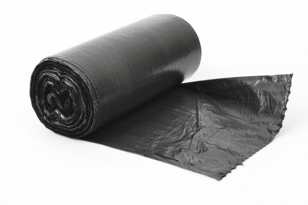 roll of black dustbin liners isolated on white background