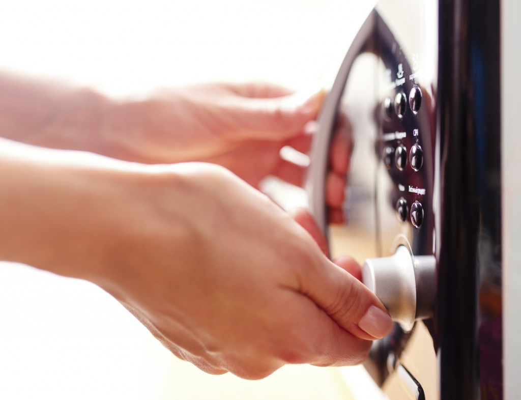 a close up image of a person turning a dial on a microwave