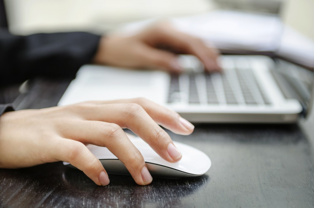 Close-up of a woman's hands on a mouse and keyboard