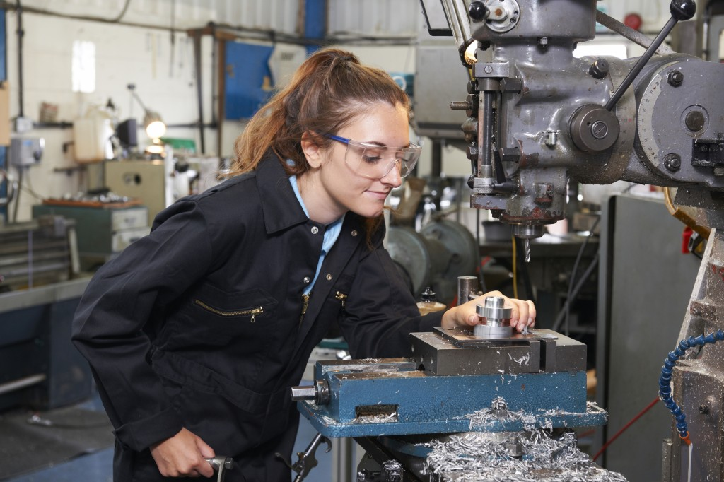 An apprentice looking over machines in a factory