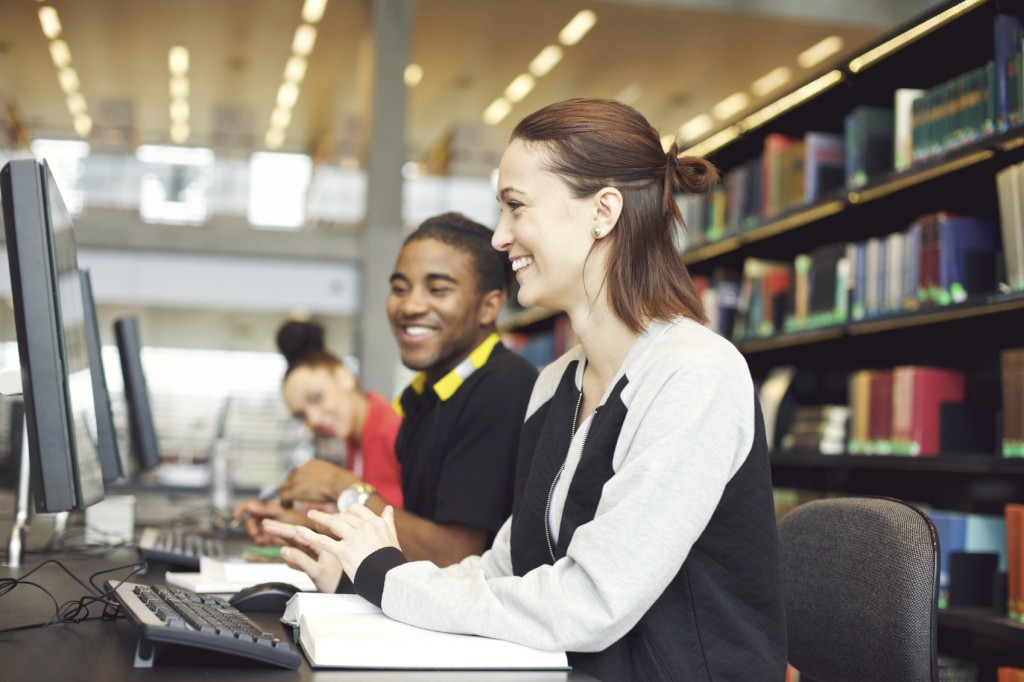 two students looking at computers in the library