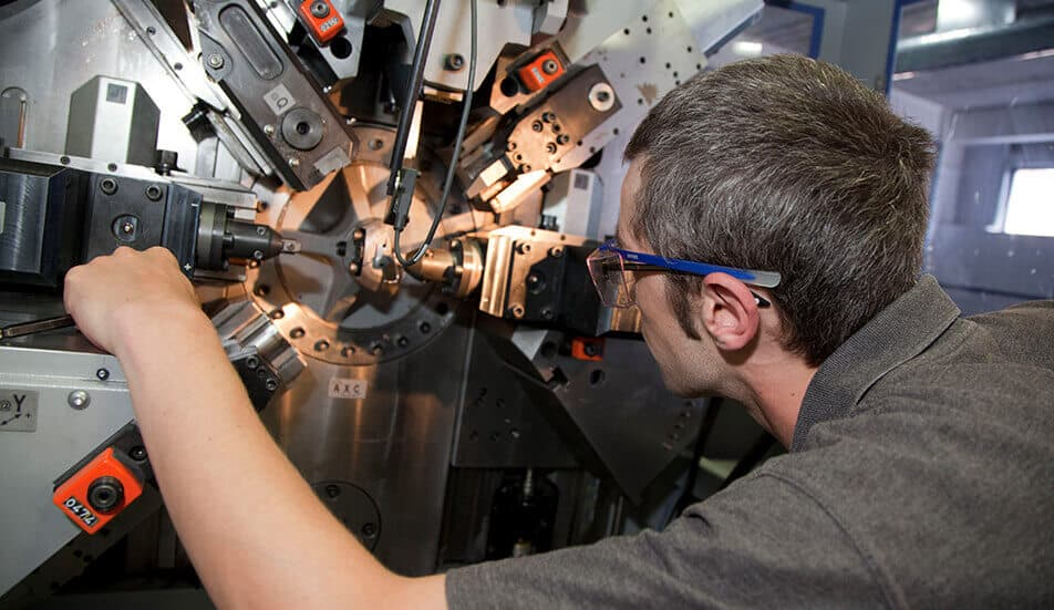 man operating cnc equipment to manufacture springs