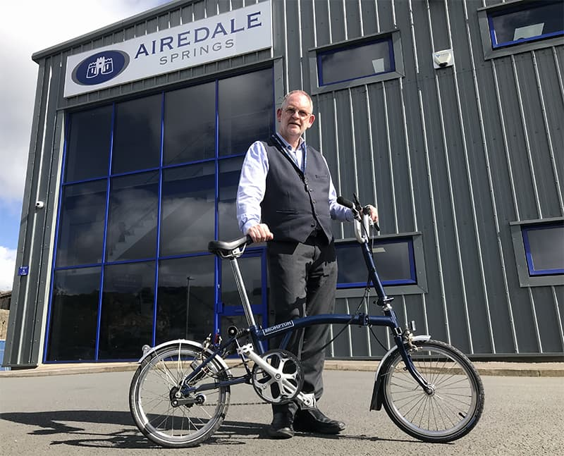 chairman stood infront of Airedale Springs manufacturing facility holding brompton bike