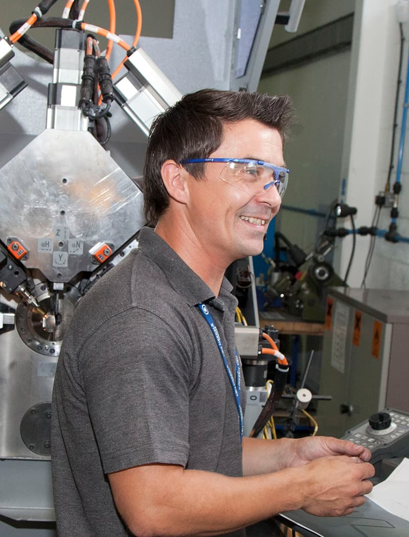 Airedale springs employee standing at a cnc machine