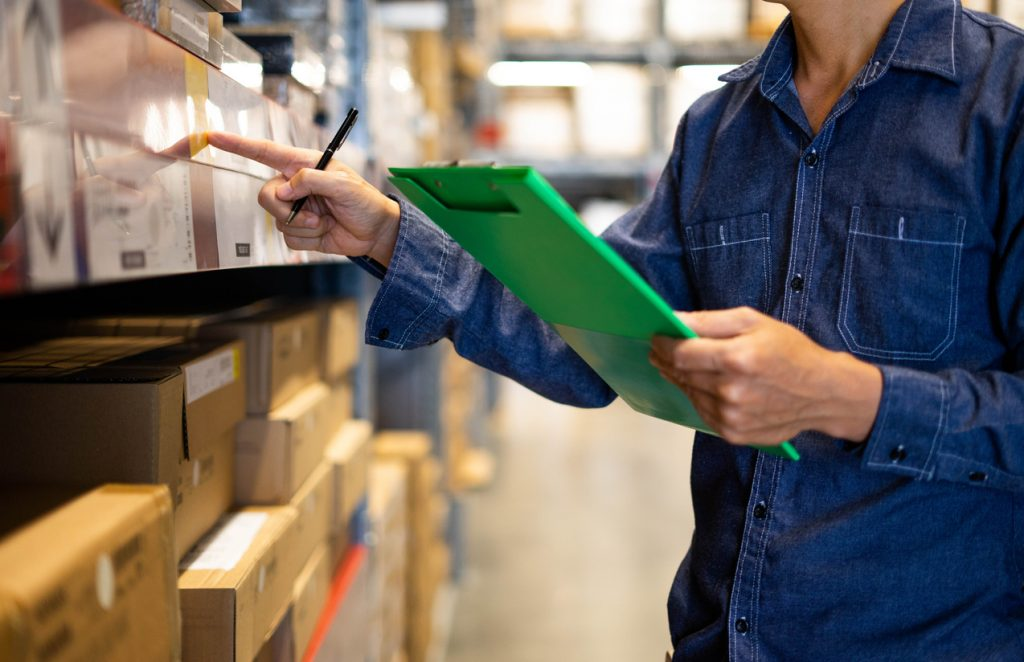 """Manager man worker doing stocktaking of product management in cardboard box on shelves in warehouse. Physical inventory count.""""n Male professional assistant checking stock in factory."""